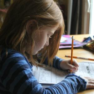 Girl drawing at a table with a pencil